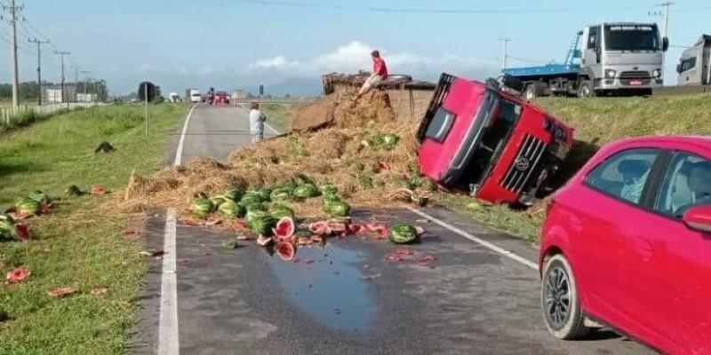 Caminhão carregado de melancia tomba na marginal da BR 101 em Laguna